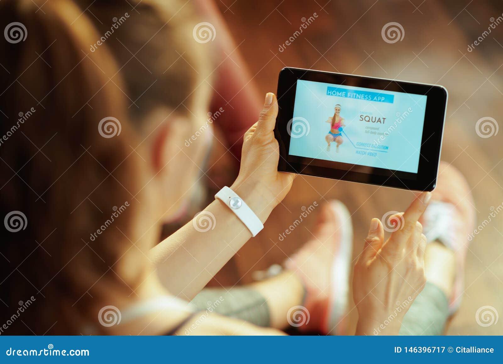使用家庭锻炼教练员应用程序的年轻体育妇女在平板电脑