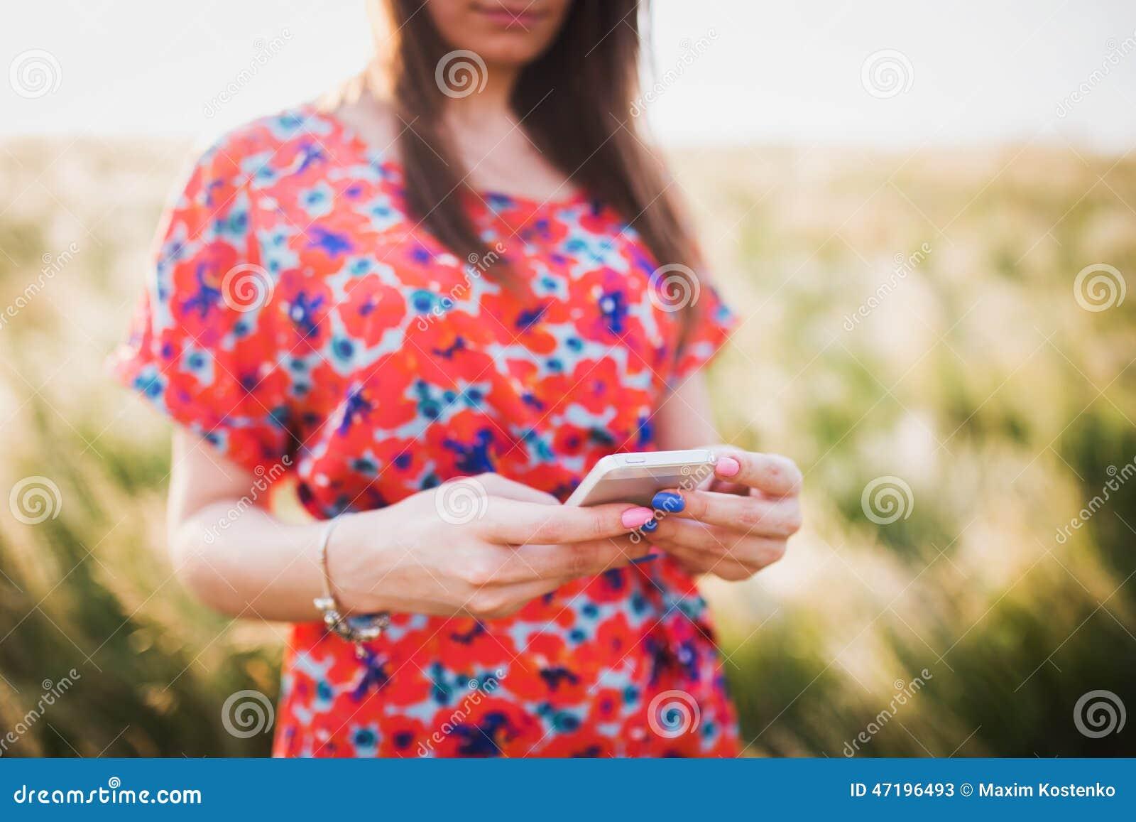 使用对流动巧妙的电话的迷人的少妇