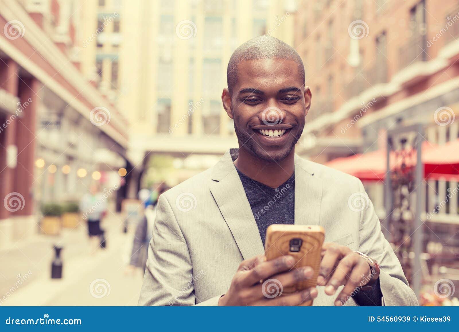 使用巧妙的电话的愉快的微笑的都市专业人