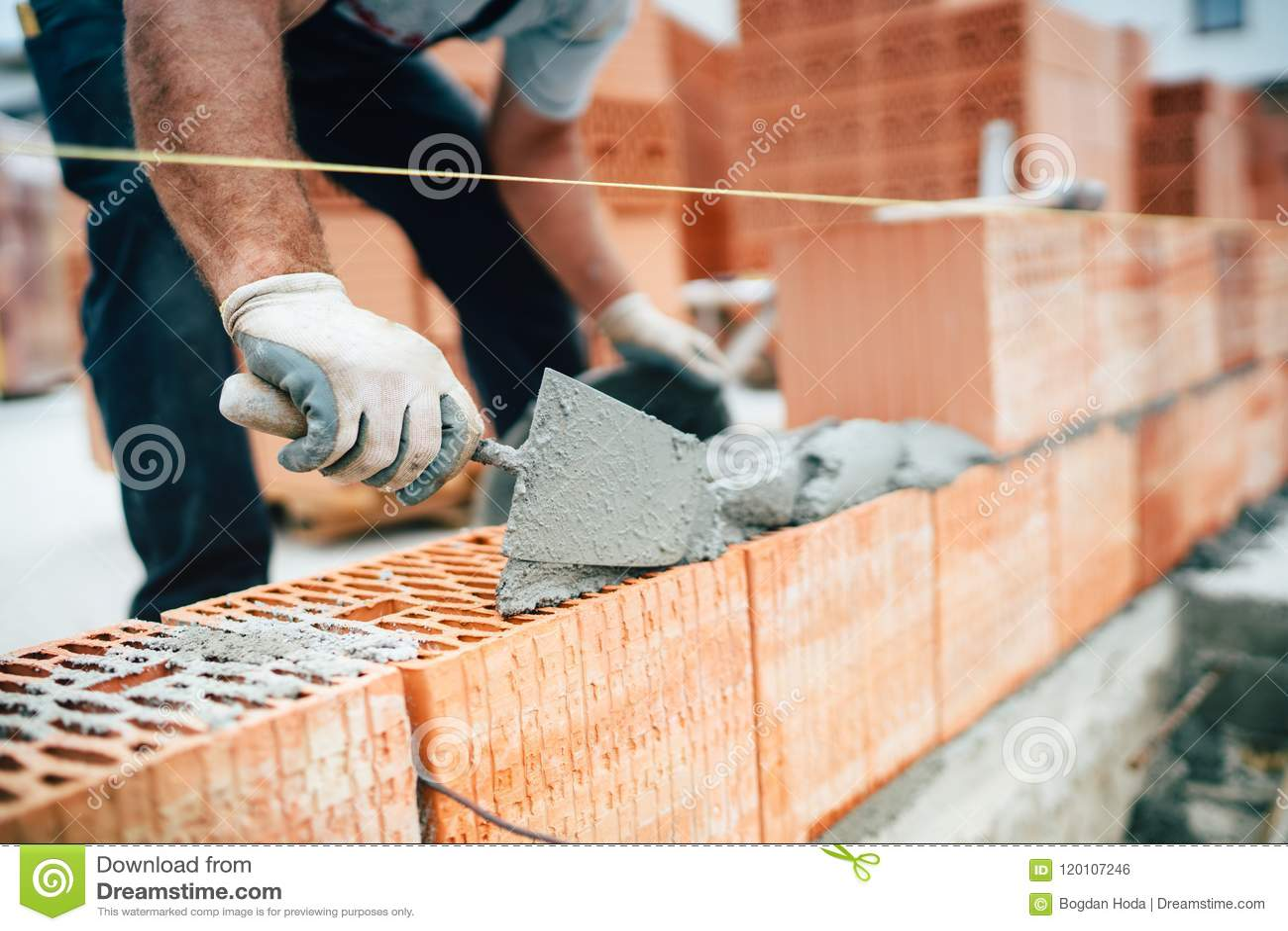 使用平底锅刀子的工作者为有水泥和灰浆的修造的砖墙