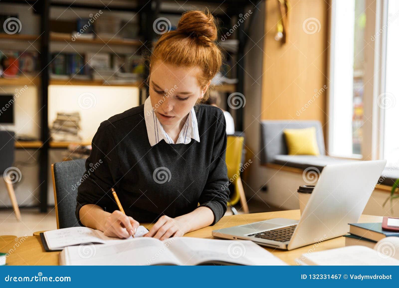 使用手提电脑的俏丽的红发十几岁的女孩