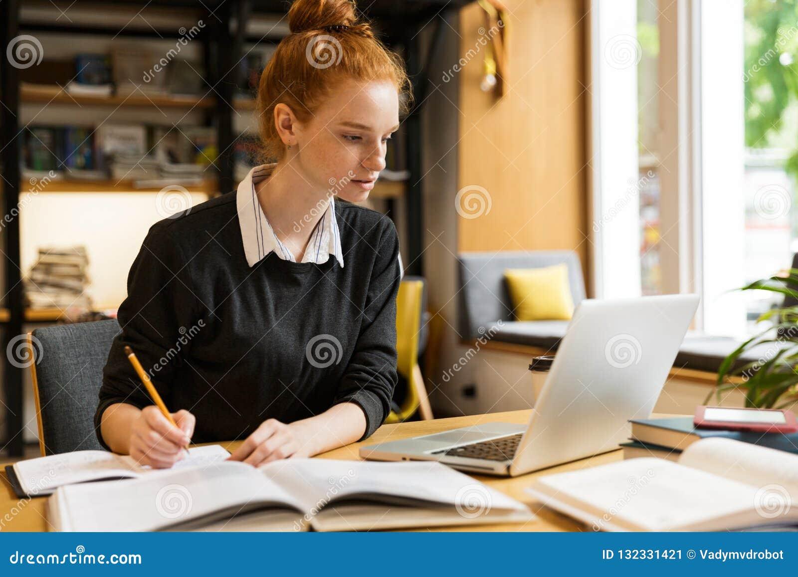 使用手提电脑的可爱的红发十几岁的女孩