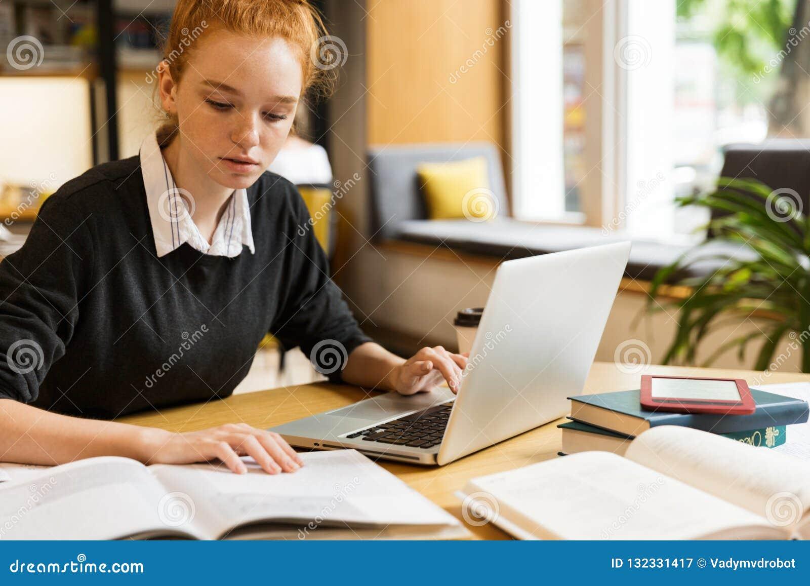 使用手提电脑的沉思红发十几岁的女孩