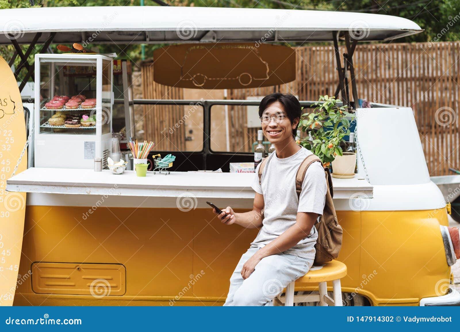 使用手机的微笑的亚裔人