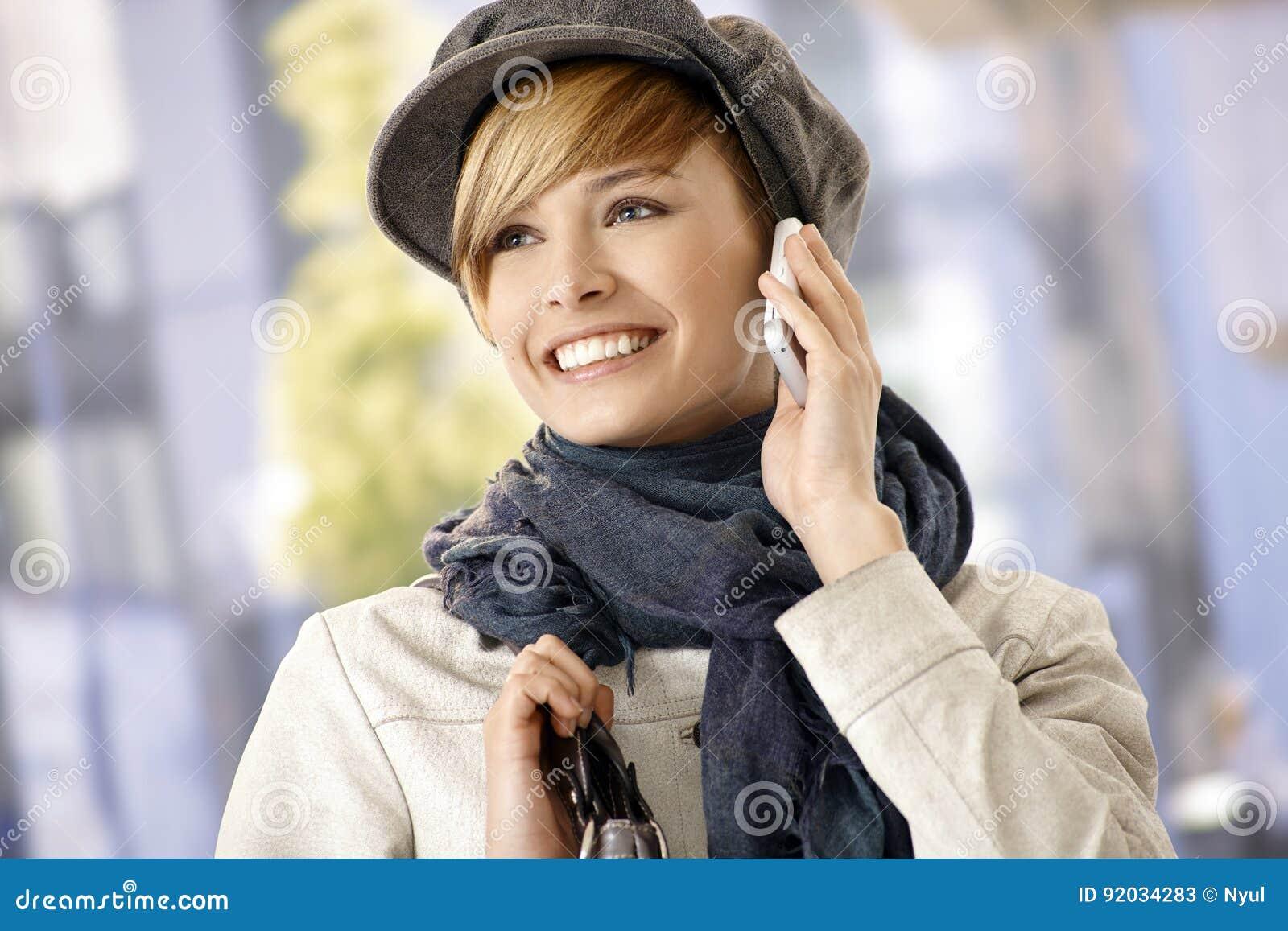 使用手机的愉快的少妇户外