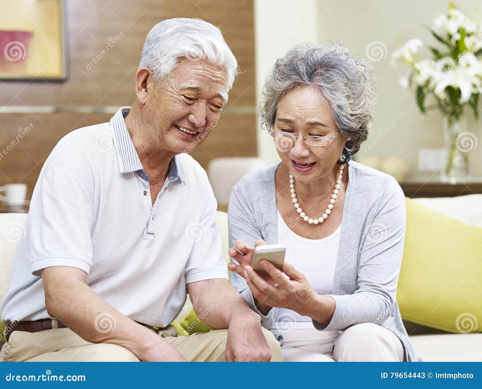 使用手机的资深亚洲夫妇在家