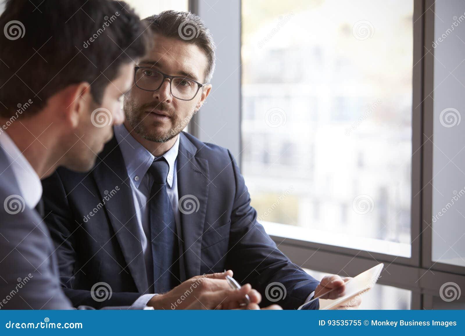 使用数字式片剂的两个商人在办公室会议
