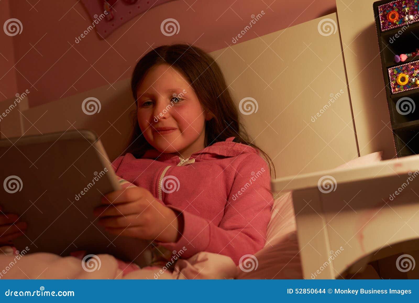 使用数字式片剂的女孩在床在晚上