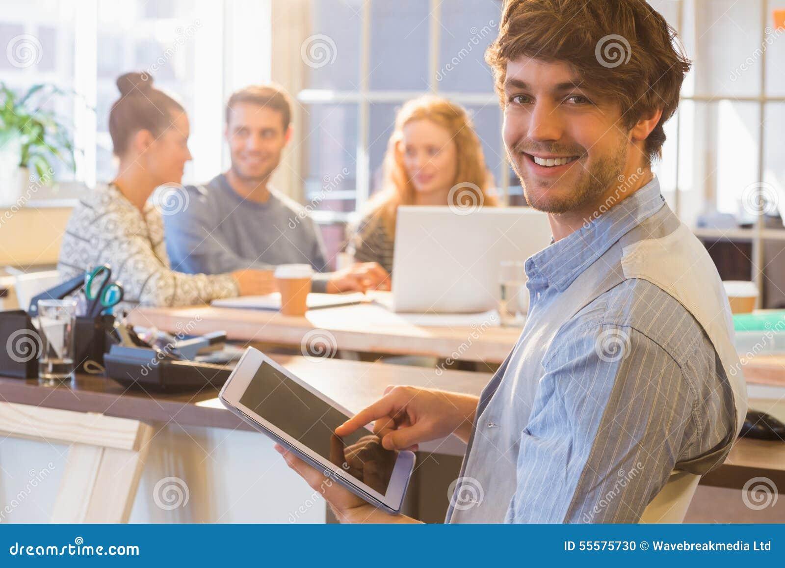 使用数字式片剂的微笑的年轻人