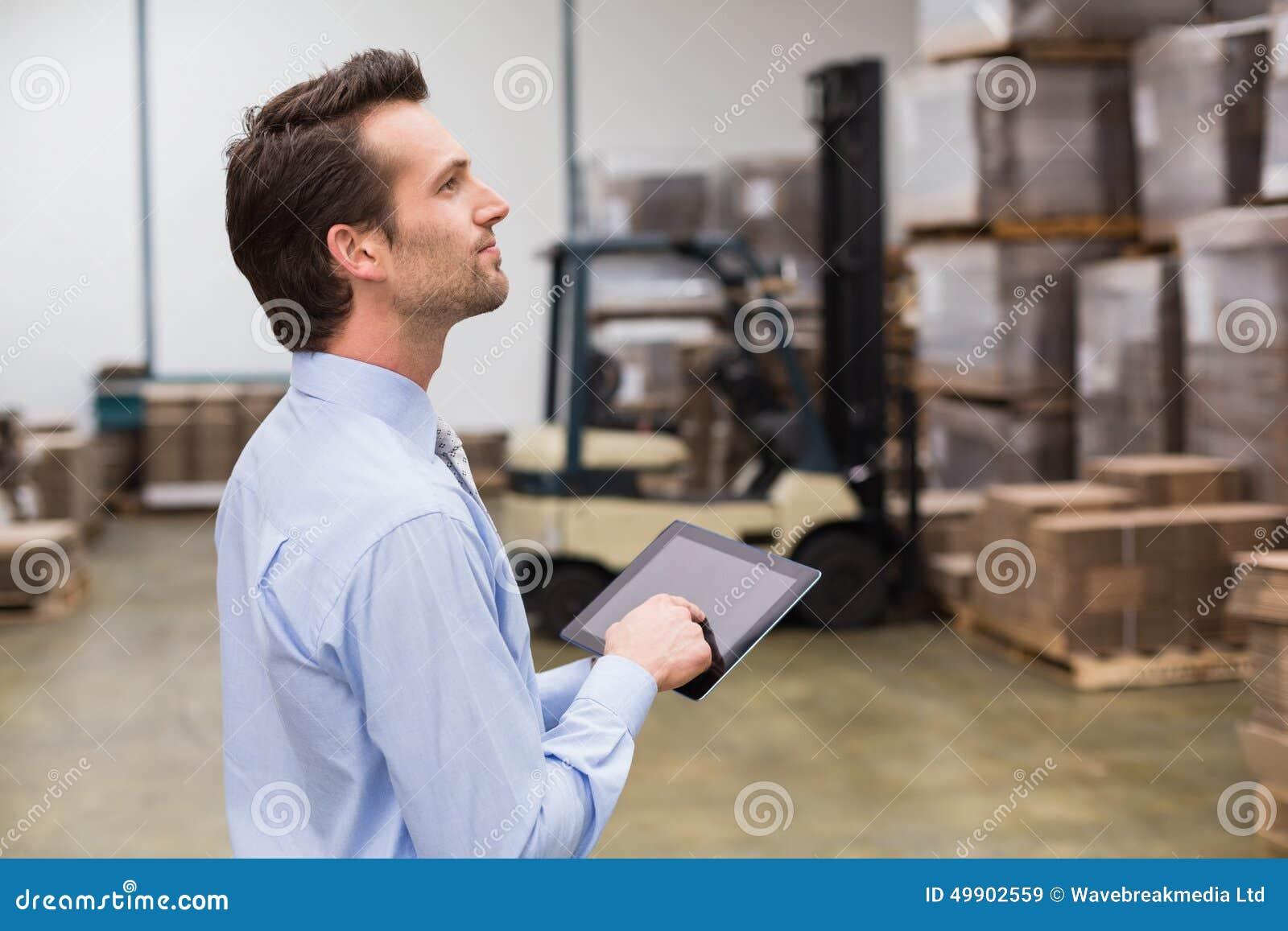 使用数字式片剂的经理在仓库