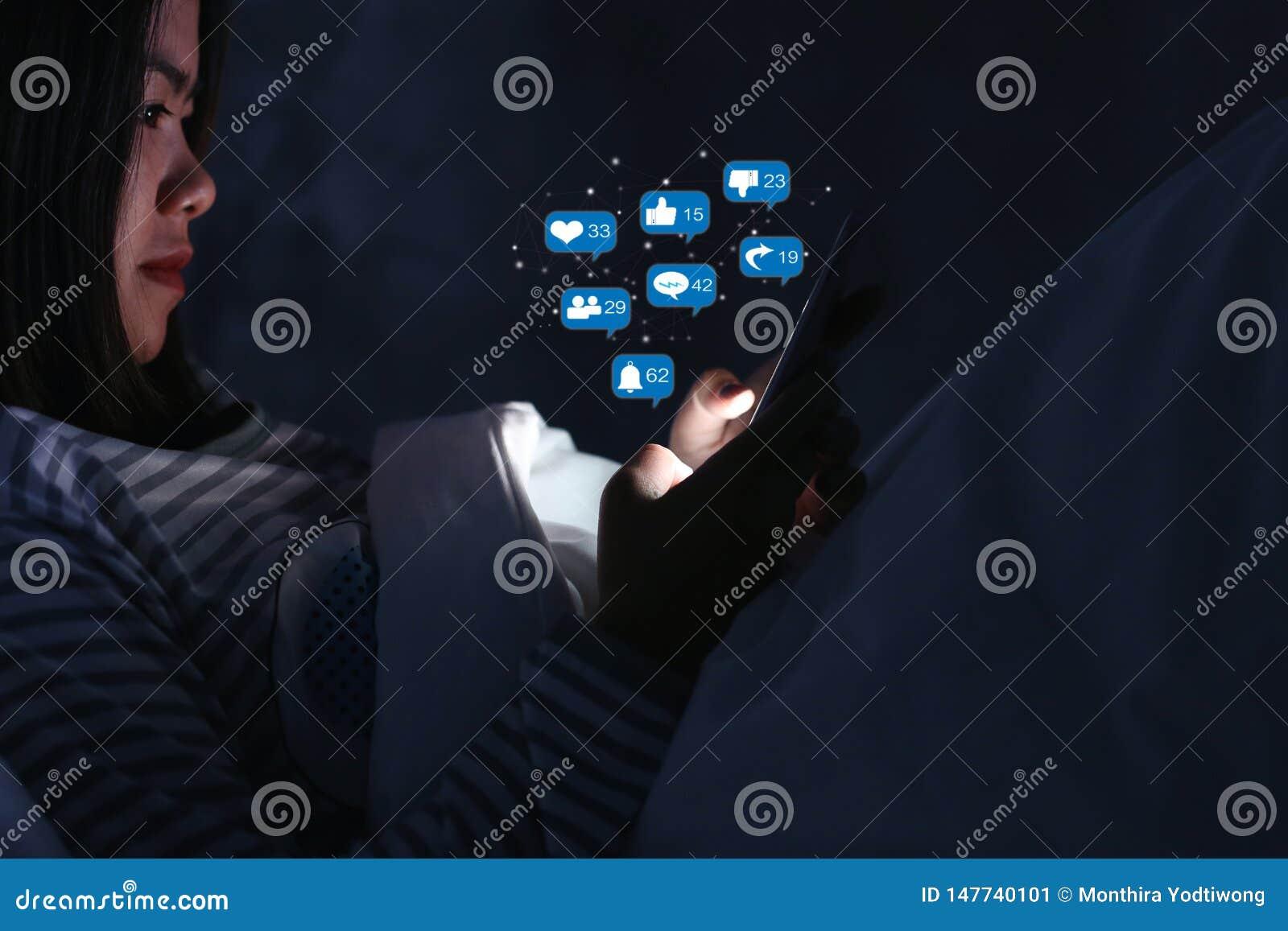 使用智能手机的亚裔妇女为检查社会媒介与象或全息图在床上的晚上在暗室,使用智能手机