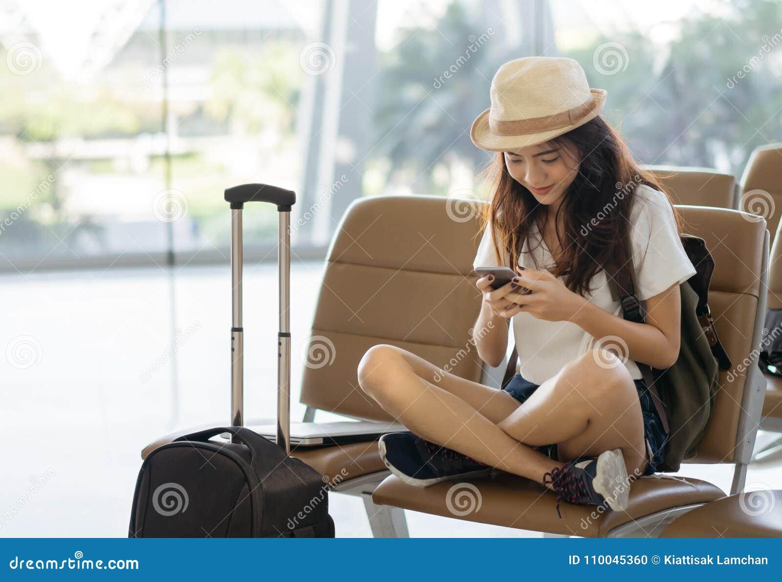 使用智能手机的亚裔妇女少年在坐与行李手提箱和背包的机场终端为旅行在假期夏天