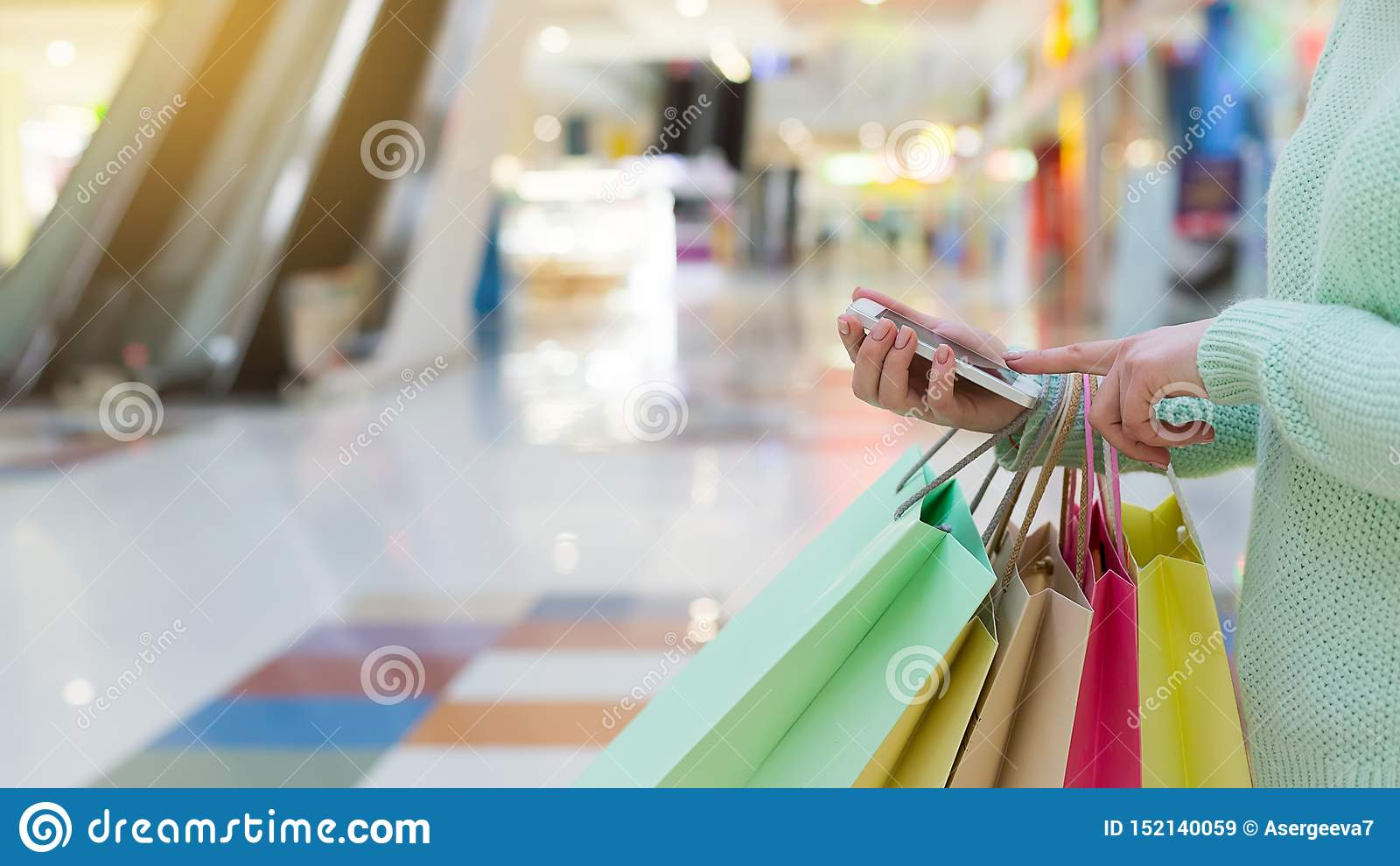 使用智能手机的妇女和拿着购物带来