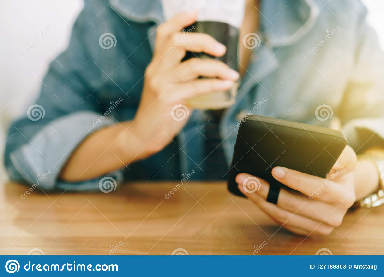 使用智能手机的妇女手,当喝与咖啡馆商店五颜六色的聚焦树荫的咖啡反对美好的backgroun时