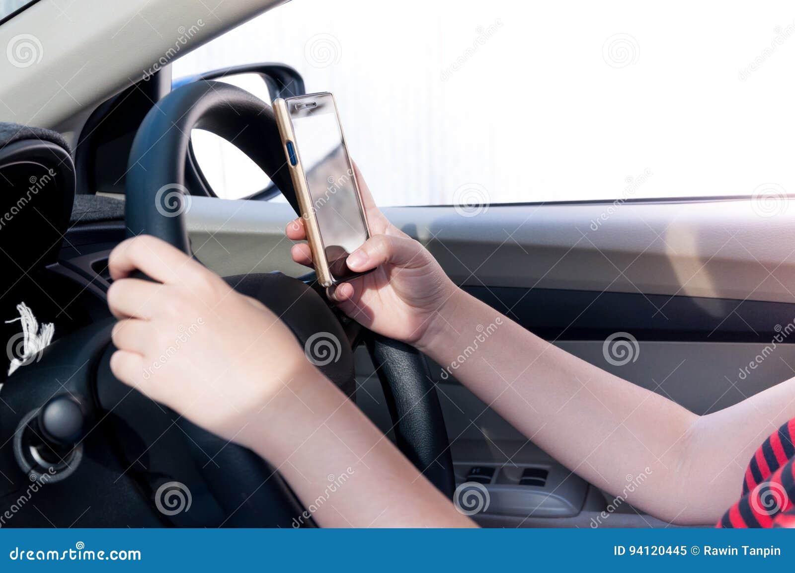 使用智能手机的妇女,当驾驶汽车在驾驶之间,因为上瘾者社交媒介时