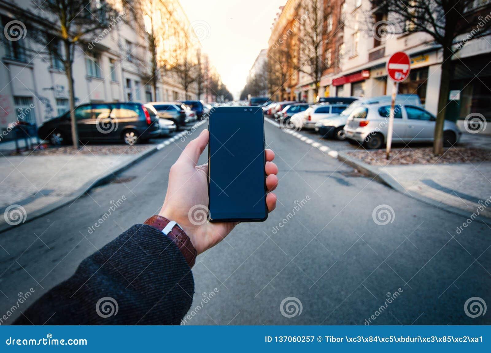 使用智能手机的男性手在街道上 技术和人脉的概念 有手表的商人,外套和采取酸碱度