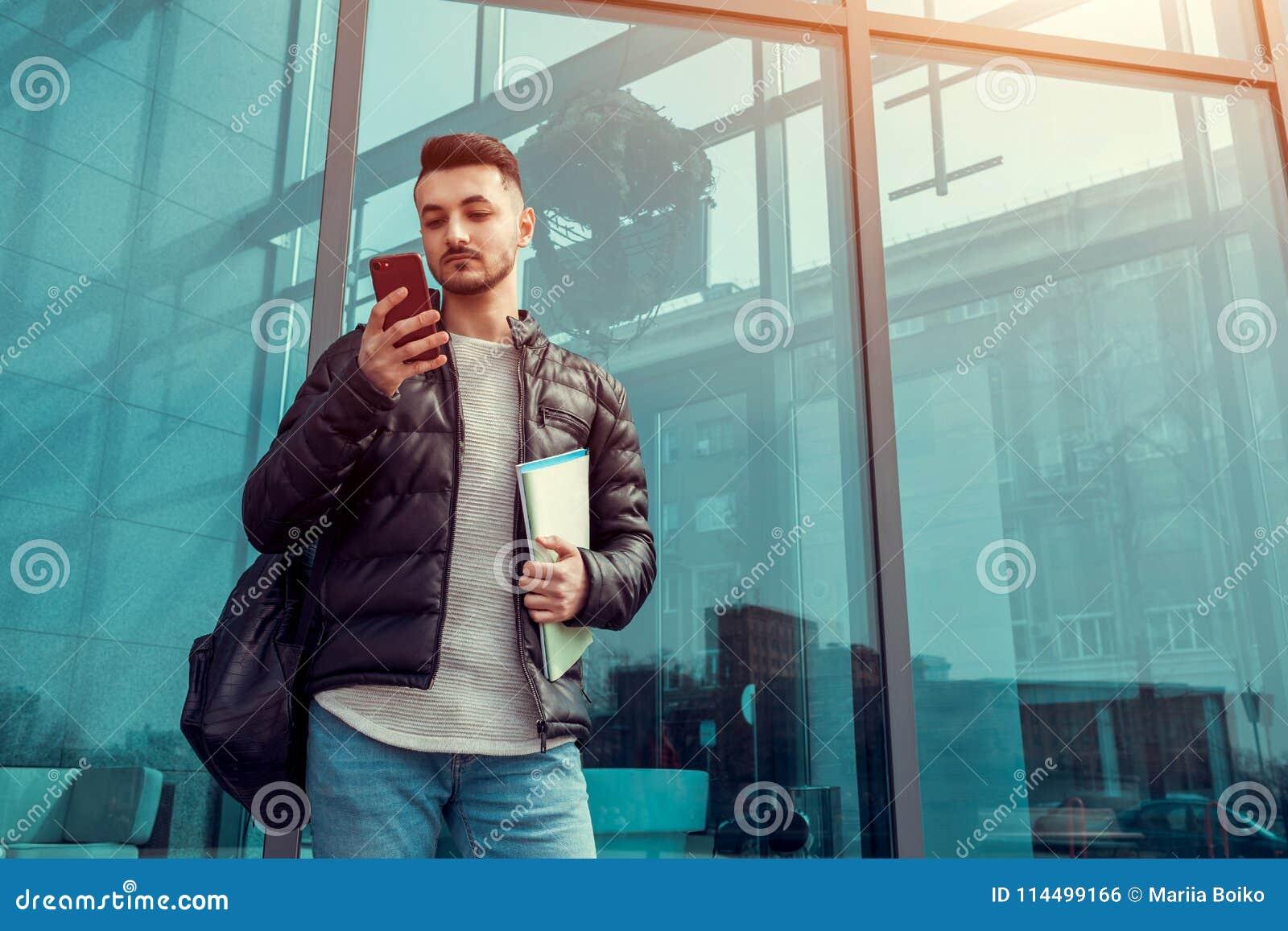 使用智能手机的阿拉伯学生外面 严肃的人看在现代大厦前面的电话在类以后