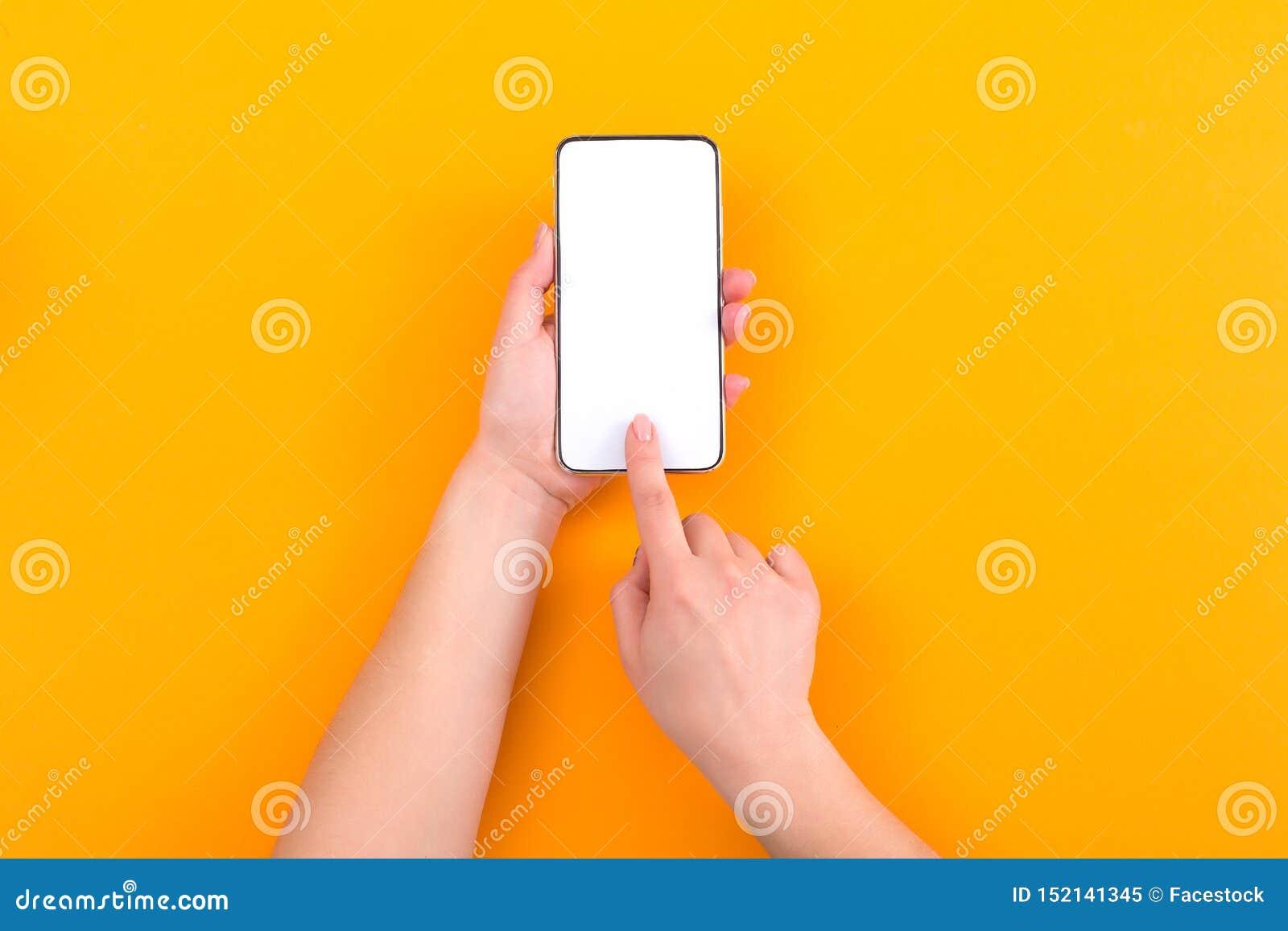 使用有空的屏幕的妇女智能手机在橙色背景 r