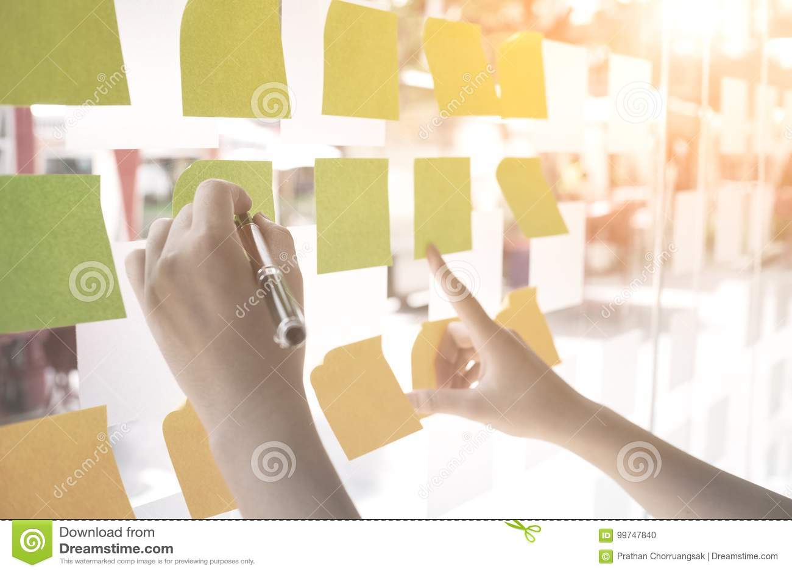 使用柱子纸笔记的手对备忘录或分享想法