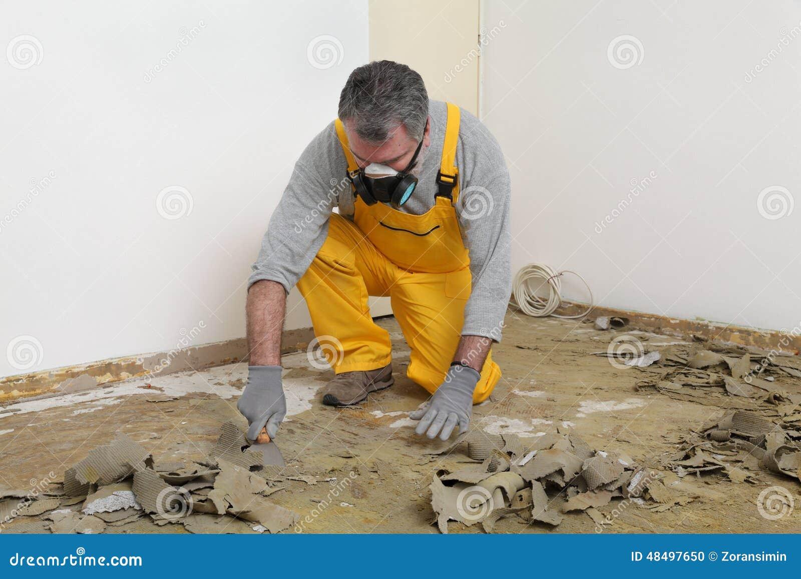 使用油灰刀的工作者为清洗的地板