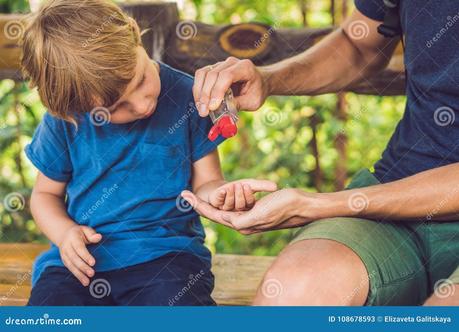 使用洗涤的父亲和儿子在快餐前递消毒剂胶凝体在公园