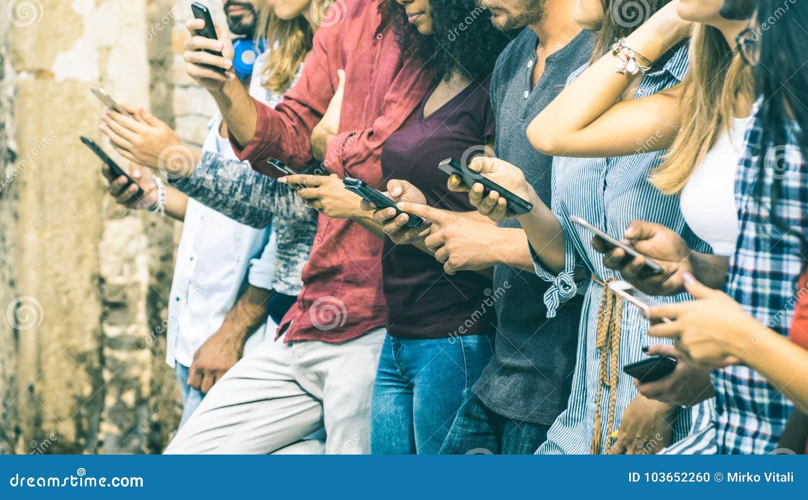 使用流动巧妙的电话的小组多文化朋友