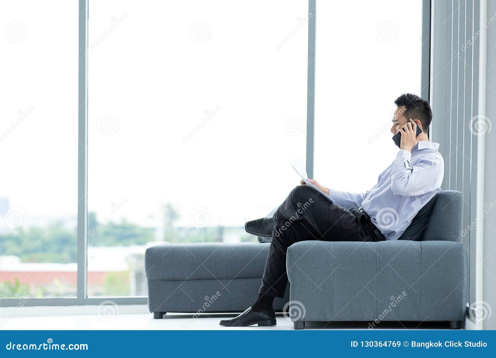 使用流动智能手机的年轻亚洲商人坐沙发