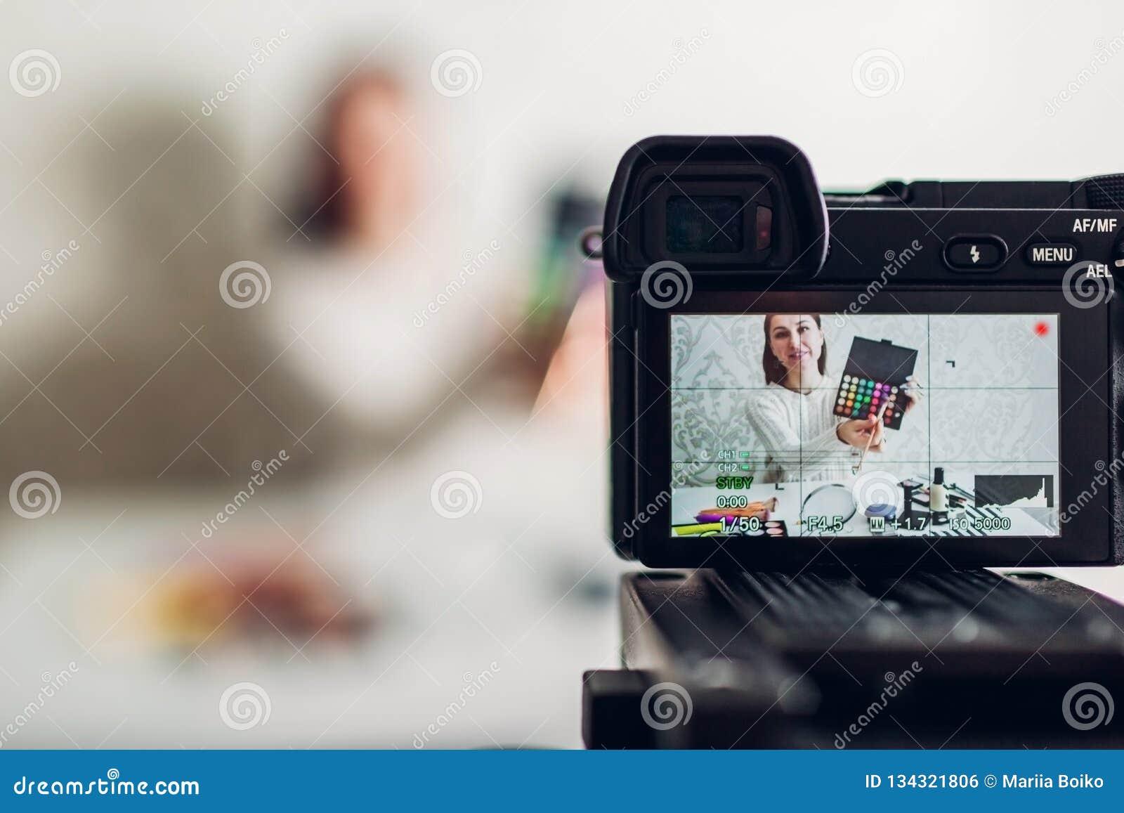 使用照相机和三脚架,年轻女人专业秀丽vlogger或博客作者录音组成讲解