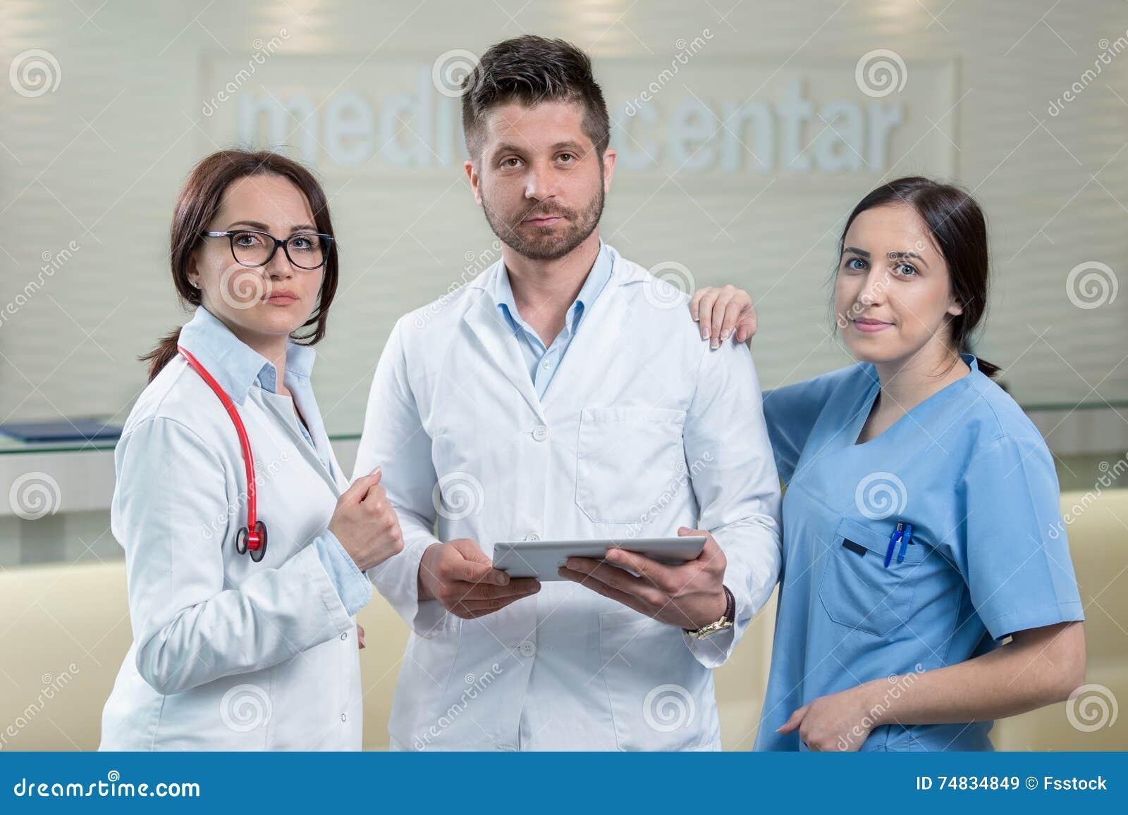 使用片剂的三位医生在一个明亮的办公室