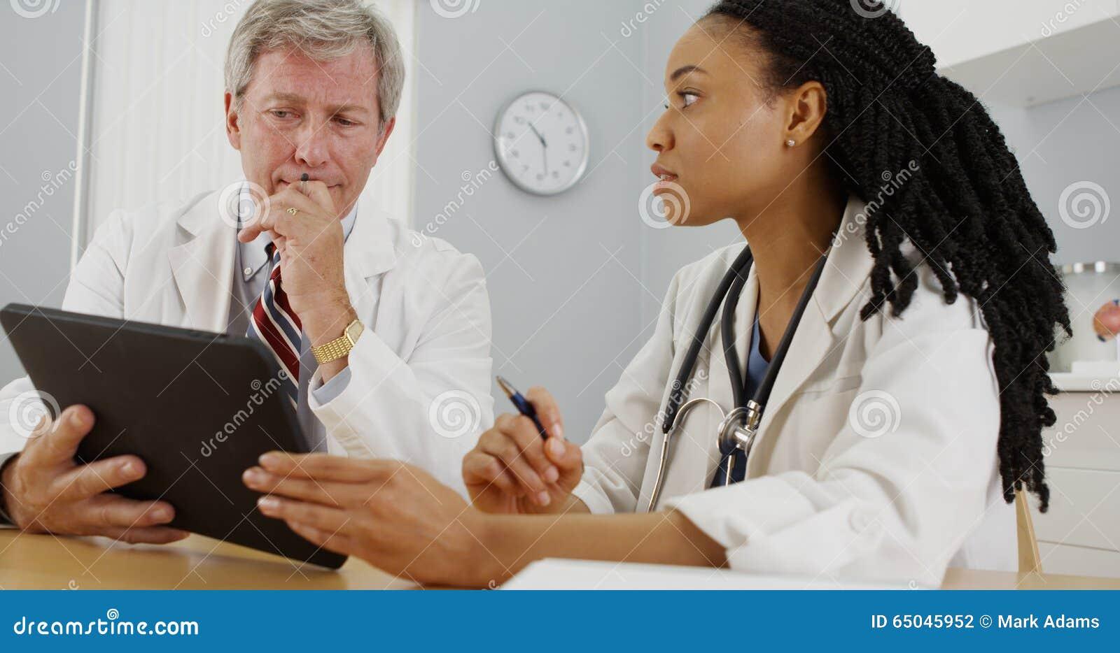 使用片剂的两位医生特写镜头在办公室
