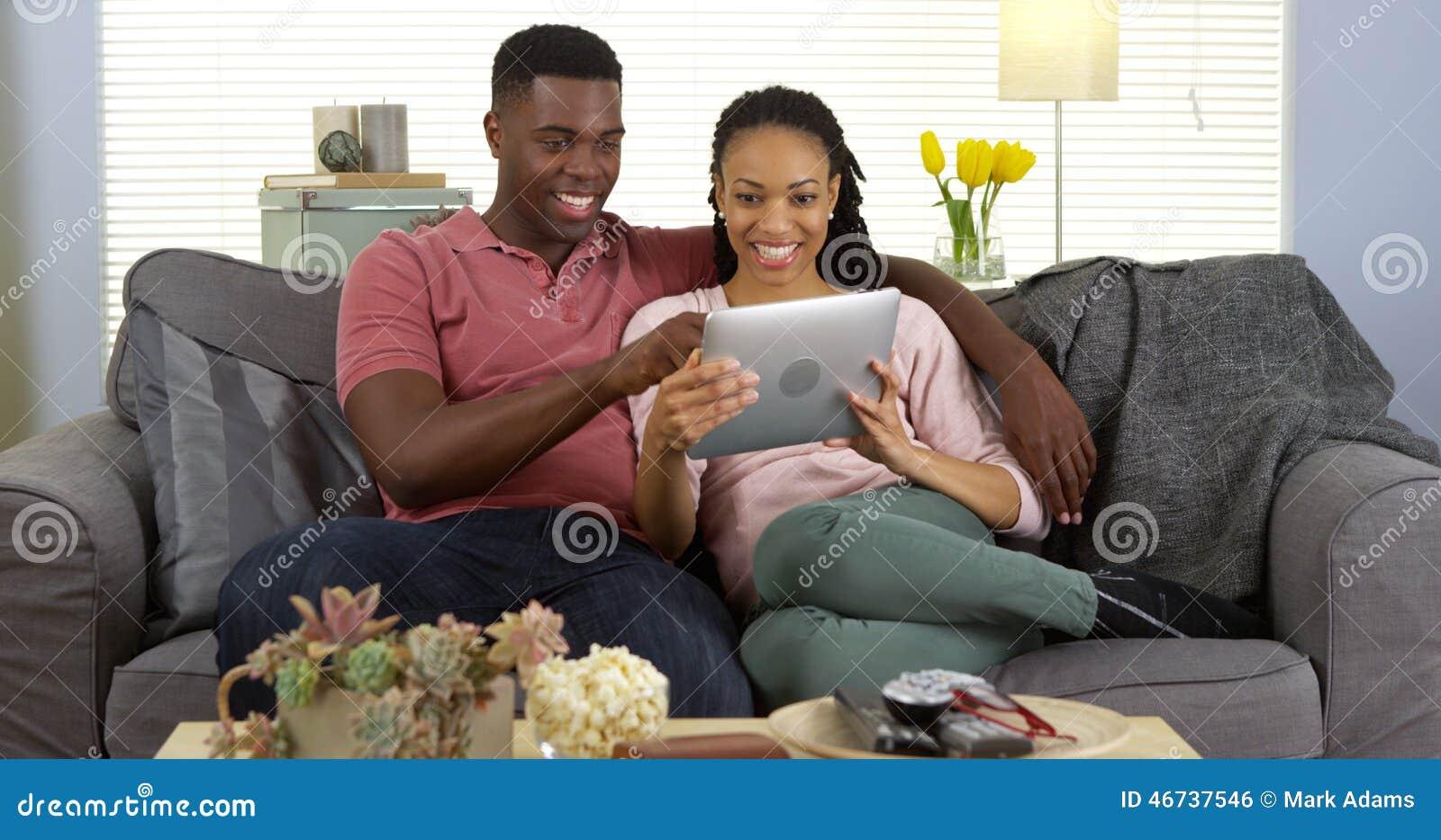 使用片剂的微笑的年轻黑夫妇在长沙发