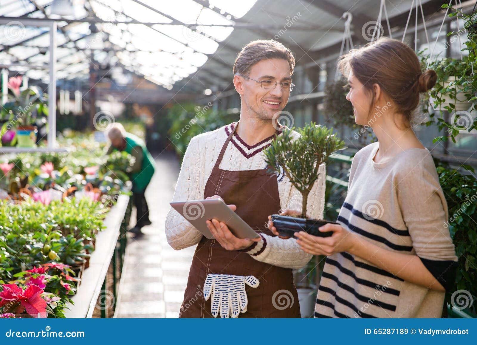 使用片剂的花匠和谈话与拿着盆景树的妇女