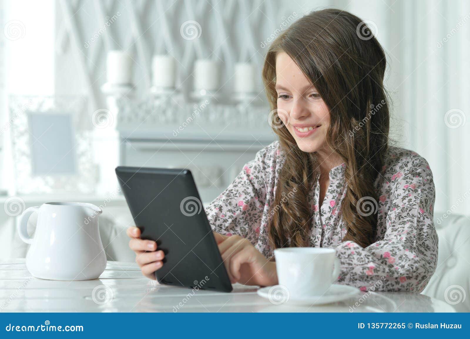 使用片剂的逗人喜爱的女孩特写镜头画象,当喝茶在轻的厨房时