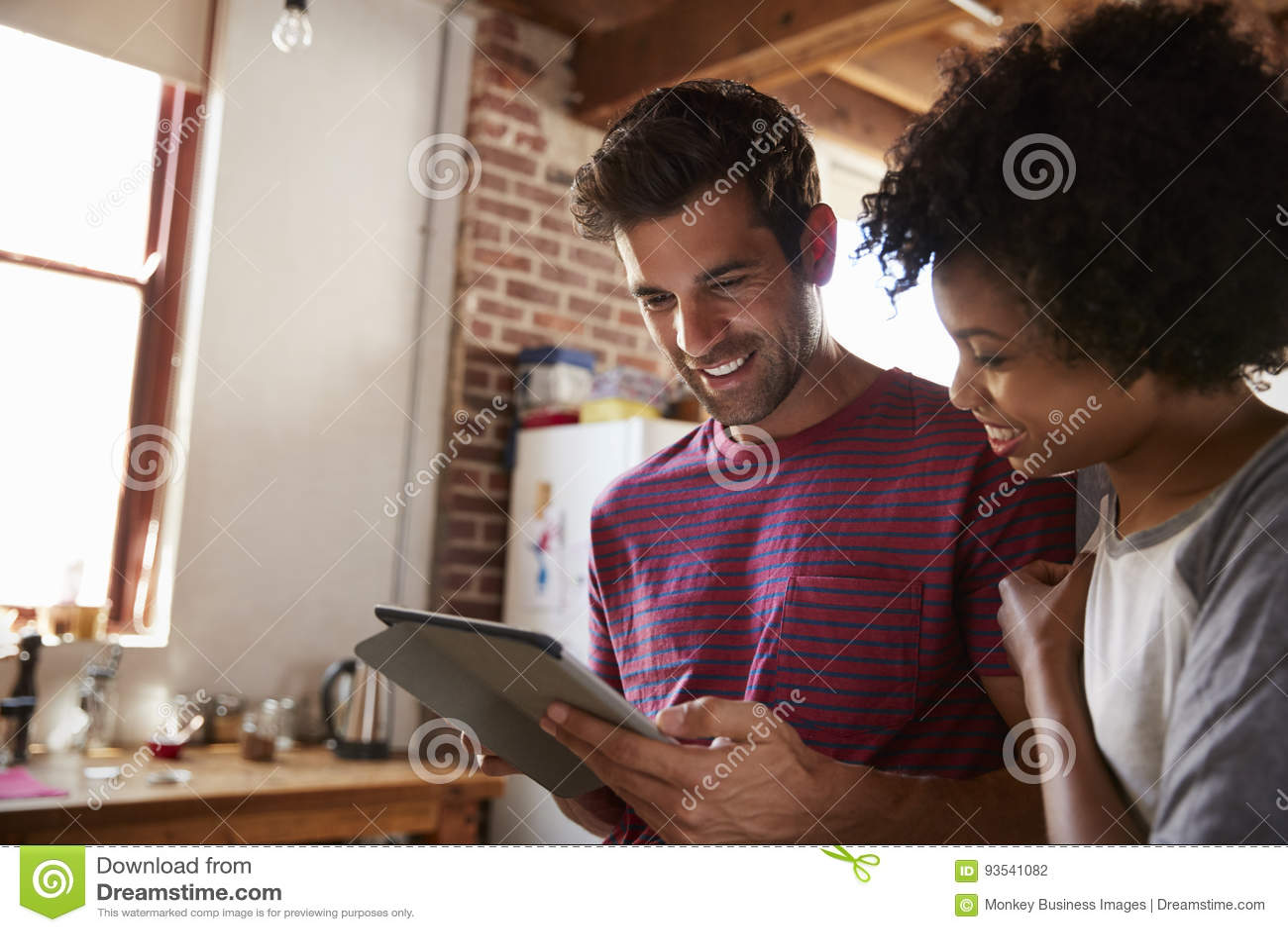 使用片剂的年轻混合的族种夫妇在厨房里,关闭
