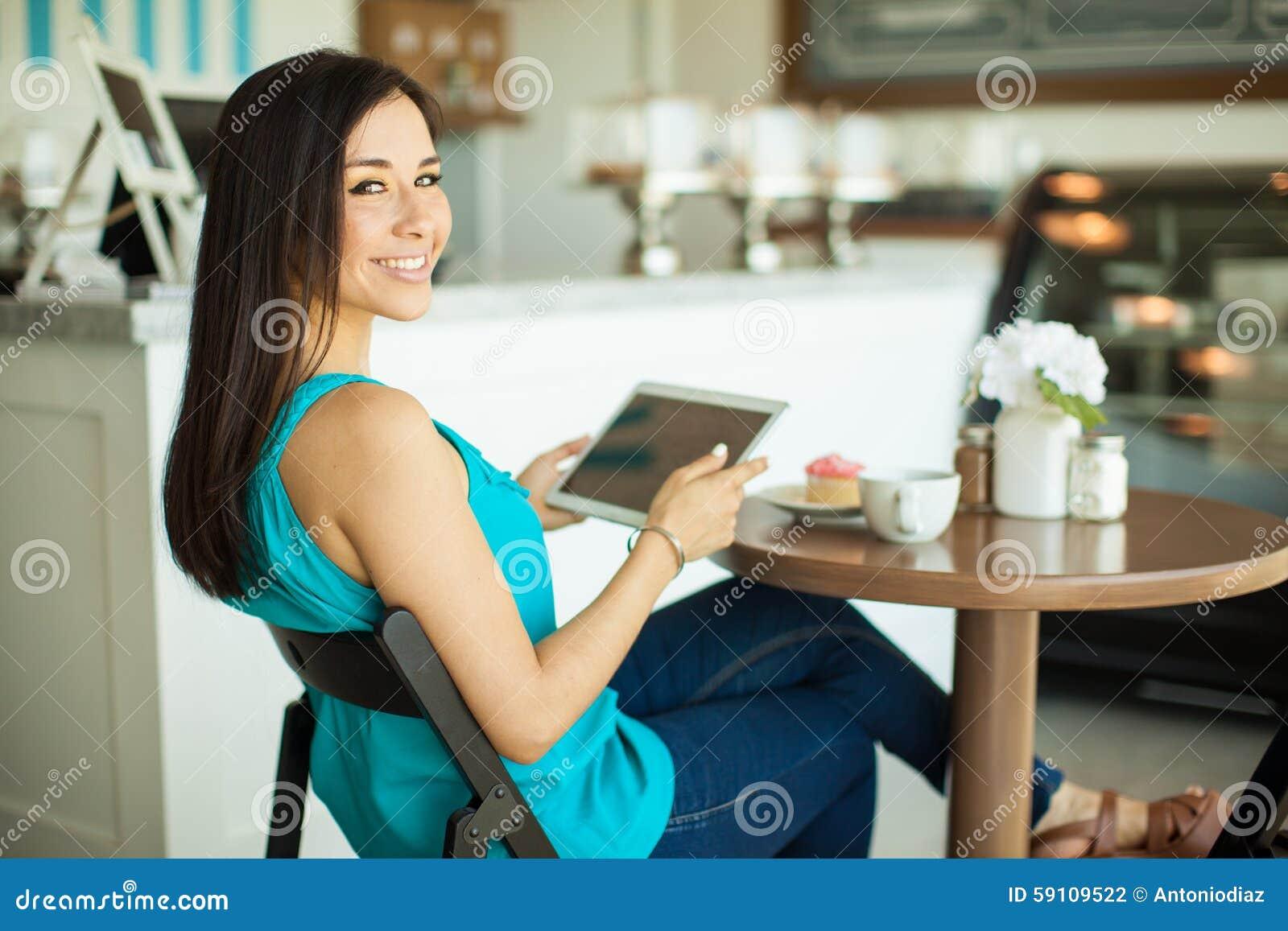 使用片剂计算机的愉快的女孩