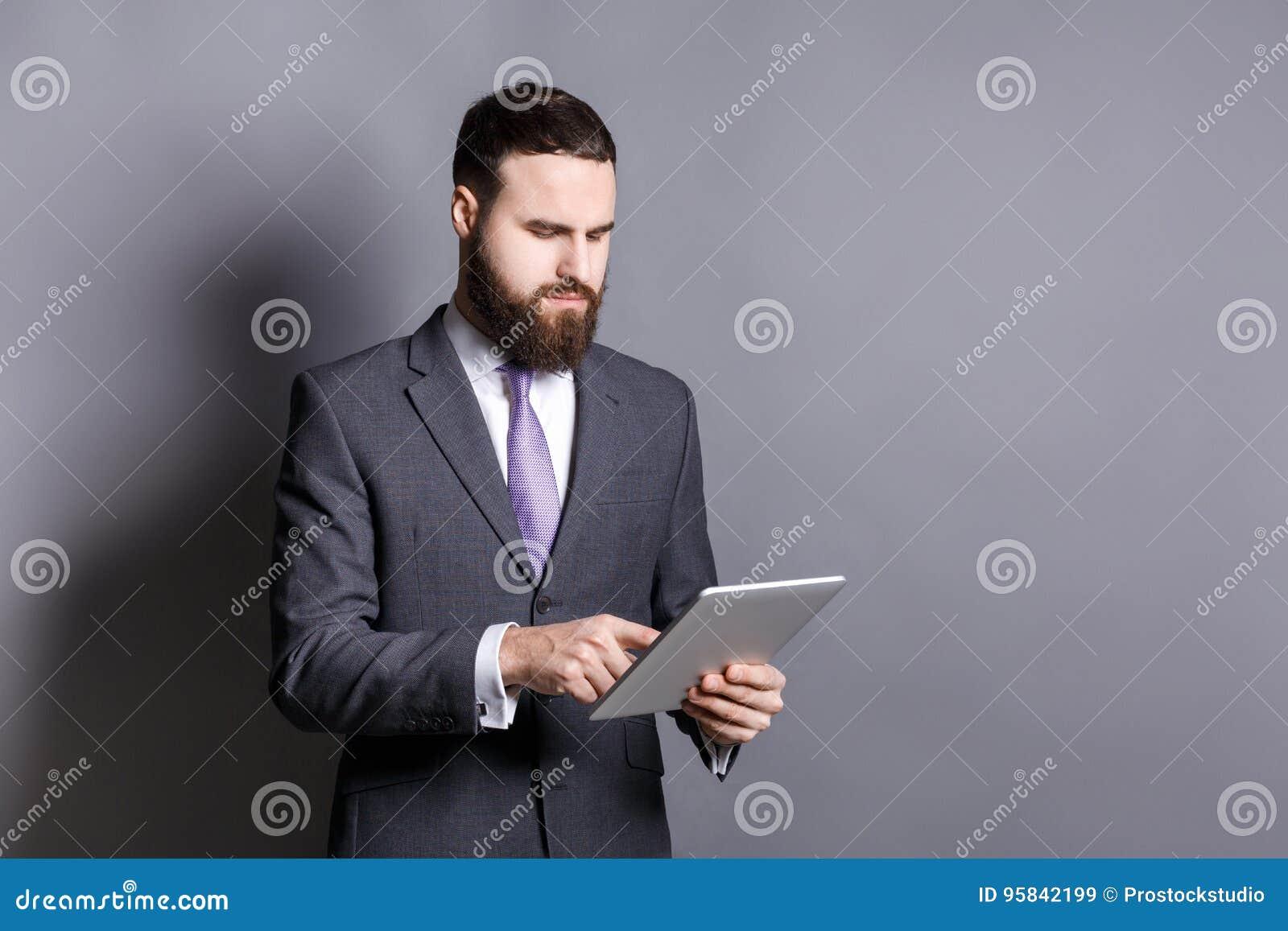使用片剂计算机的年轻有胡子的商人