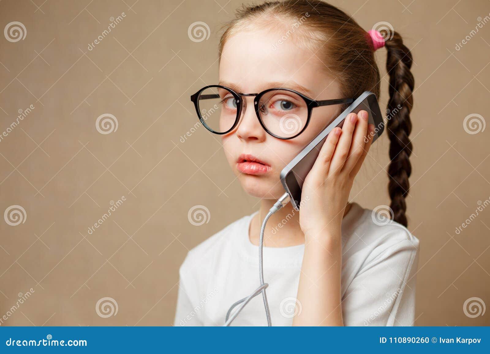 使用现代智能手机的逗人喜爱的小女孩