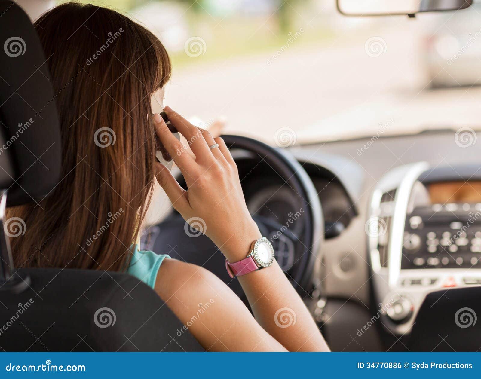 使用电话的妇女,当驾驶汽车时