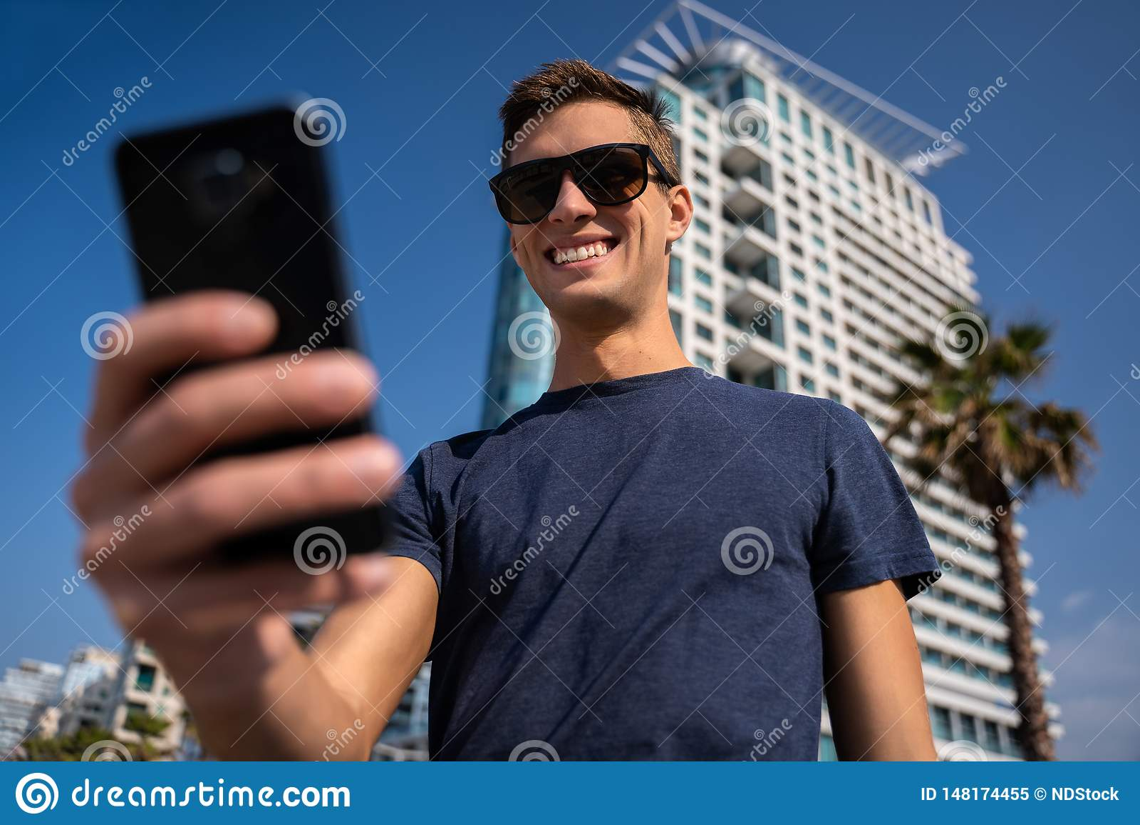 使用电话的年轻人 城市地平线在背景中