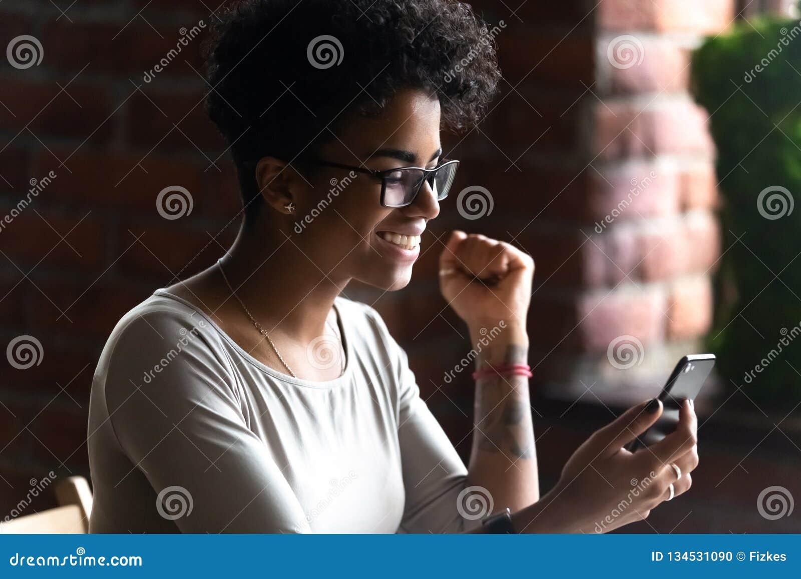 使用电话的愉快的非裔美国人的妇女,庆祝喜讯