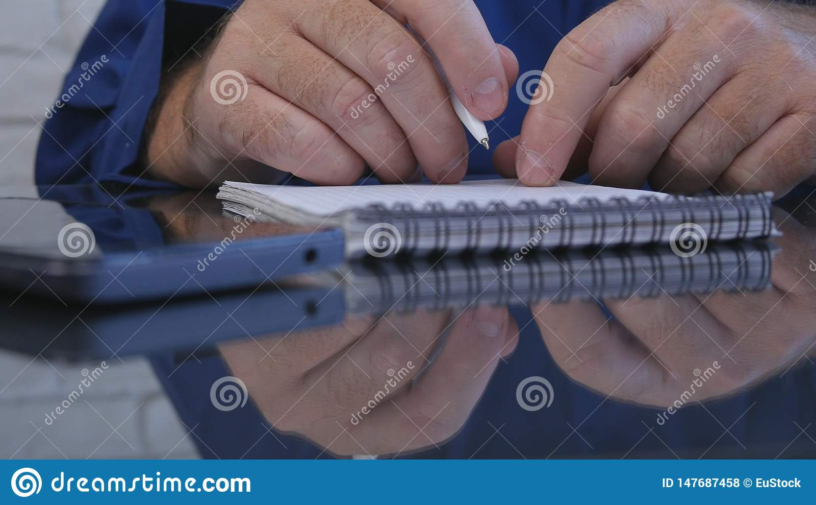 使用笔,商人工作在办公室屋子里采取在议程的笔记