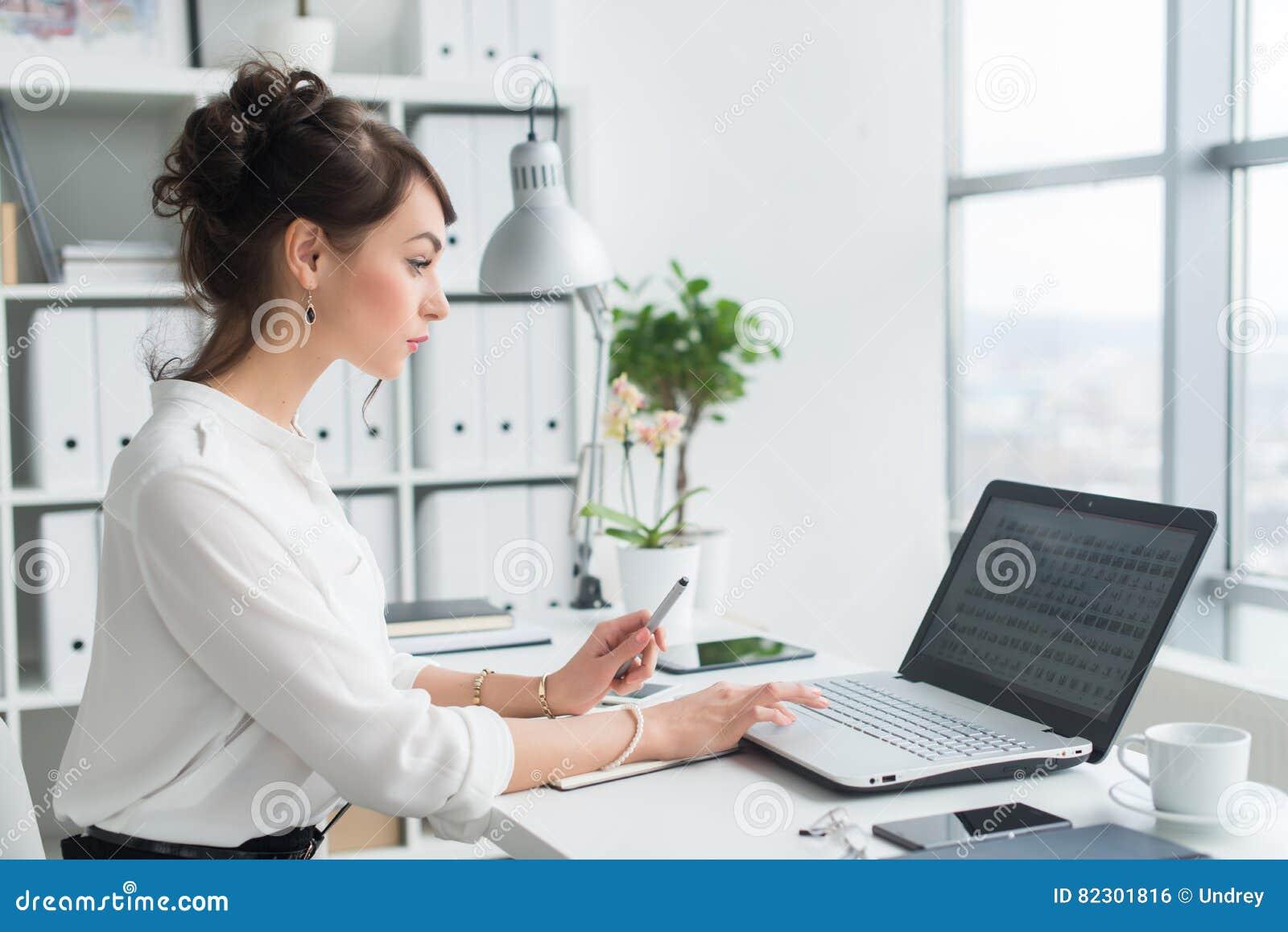 使用膝上型计算机在她的工作场所,浏览信息的女性办公室工作者,浏览互联网,侧视图画象