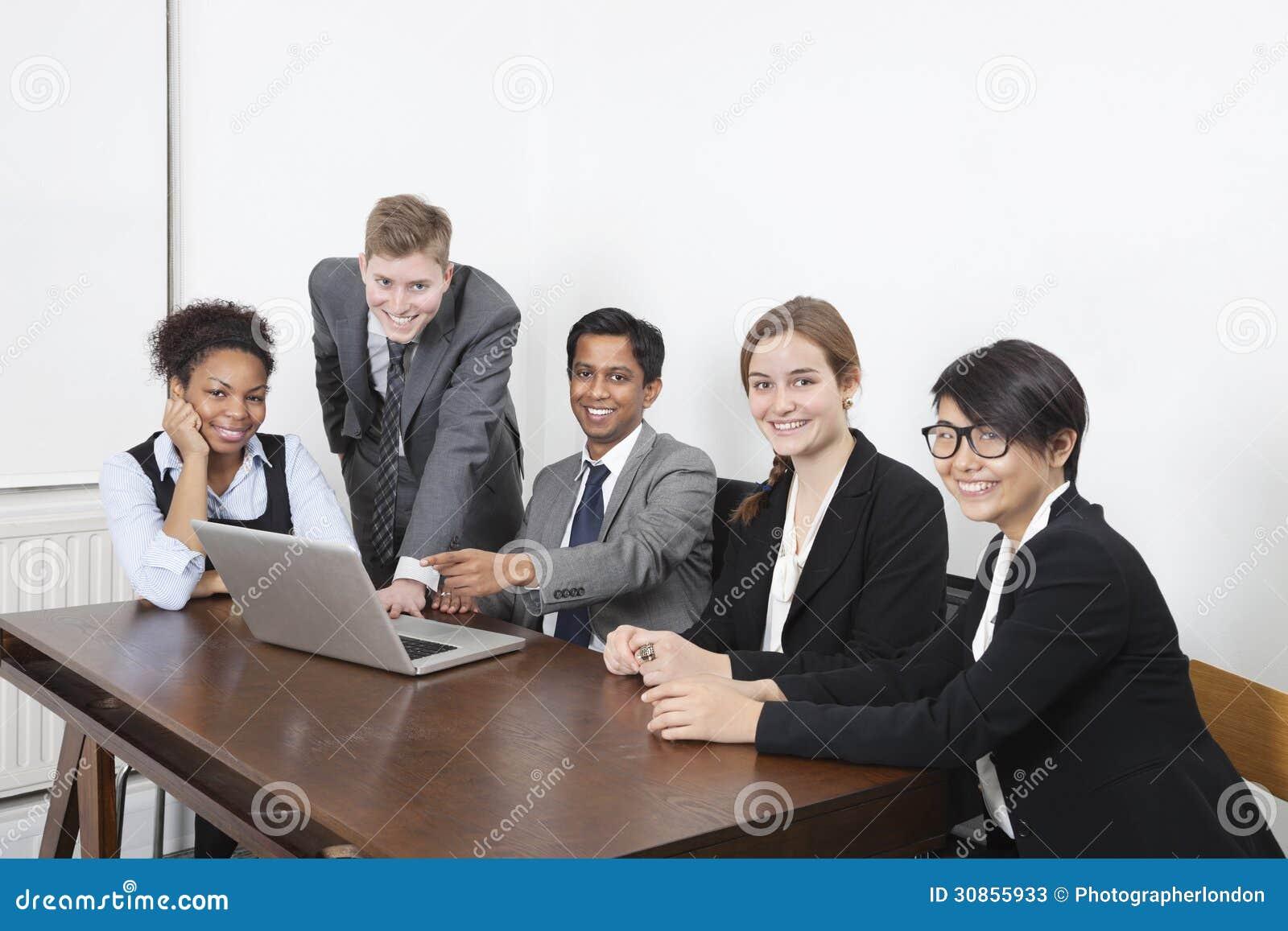 使用膝上型计算机的不同种族的专家画象在会议室