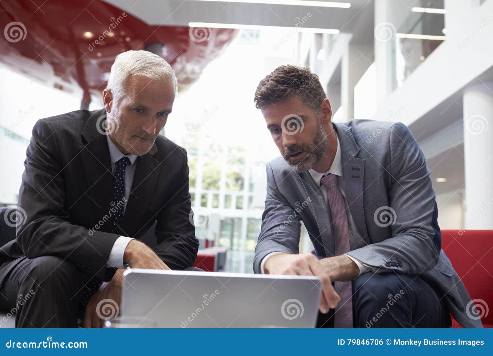 使用膝上型计算机的两个商人在现代办公室大厅地区