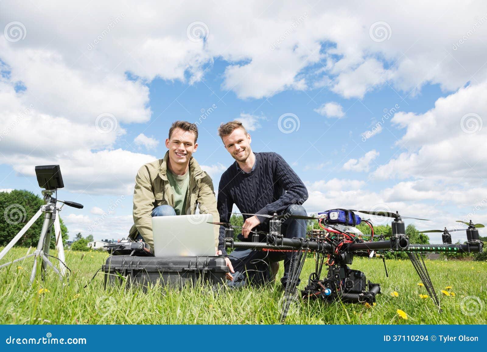 使用膝上型计算机的人在UAV旁边