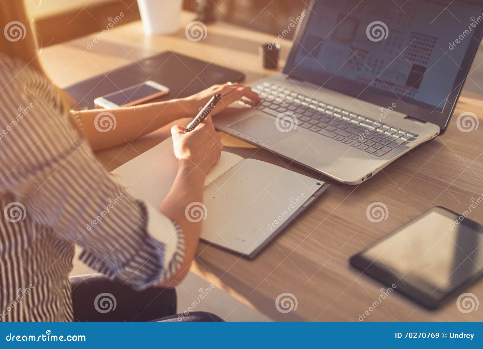 使用膝上型计算机的女性设计师,速写在空白的笔记薄 妇女在笔记本的手文字在木书桌上