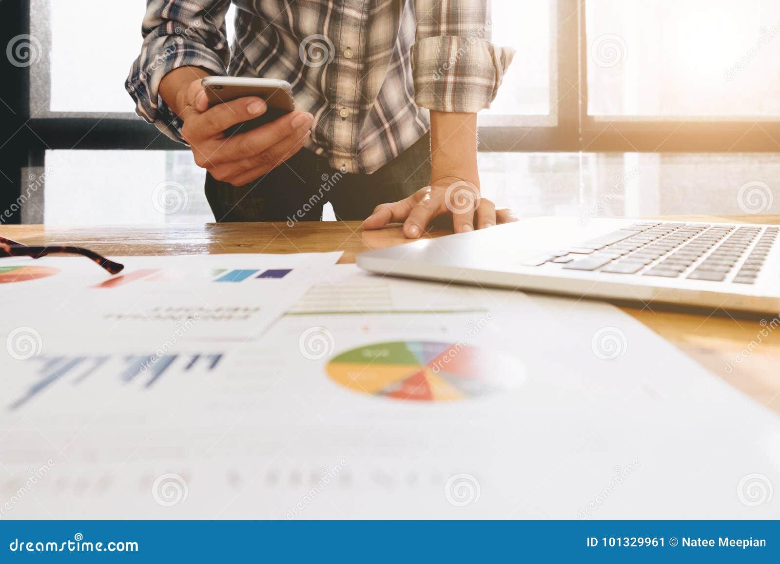 使用膝上型计算机的年轻人,当拿着智能手机时 图表和炭灰