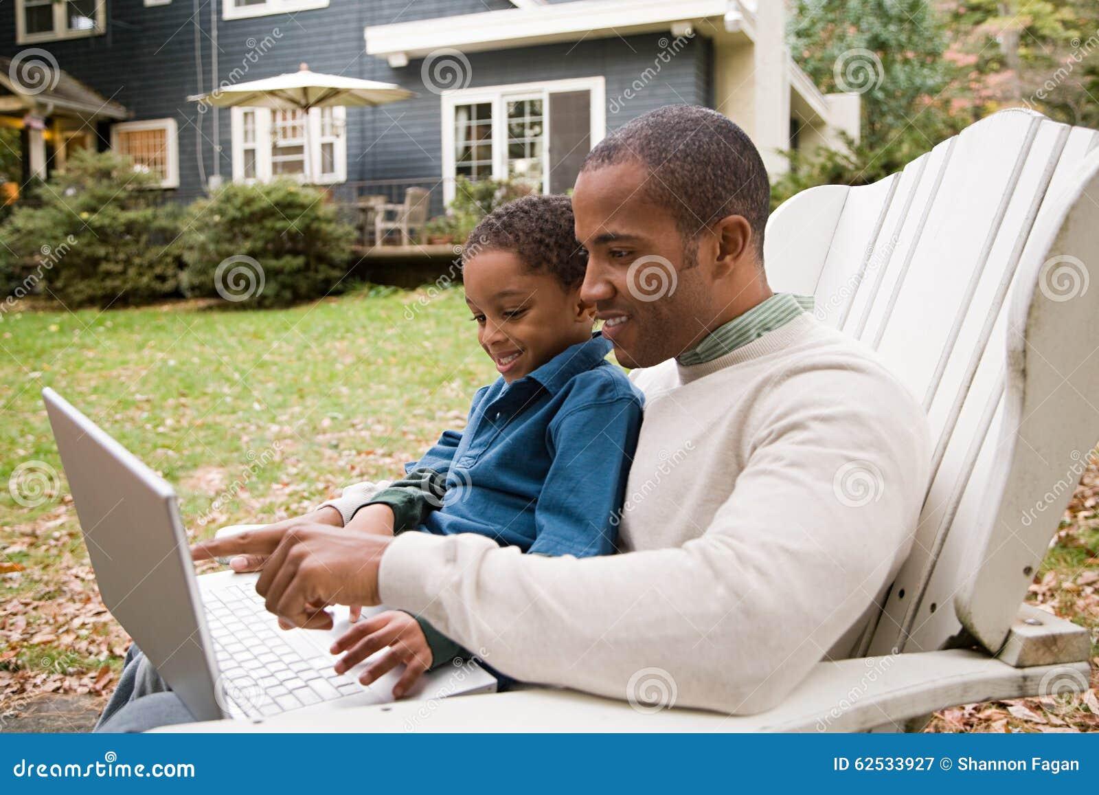 使用膝上型计算机的父亲和儿子在庭院