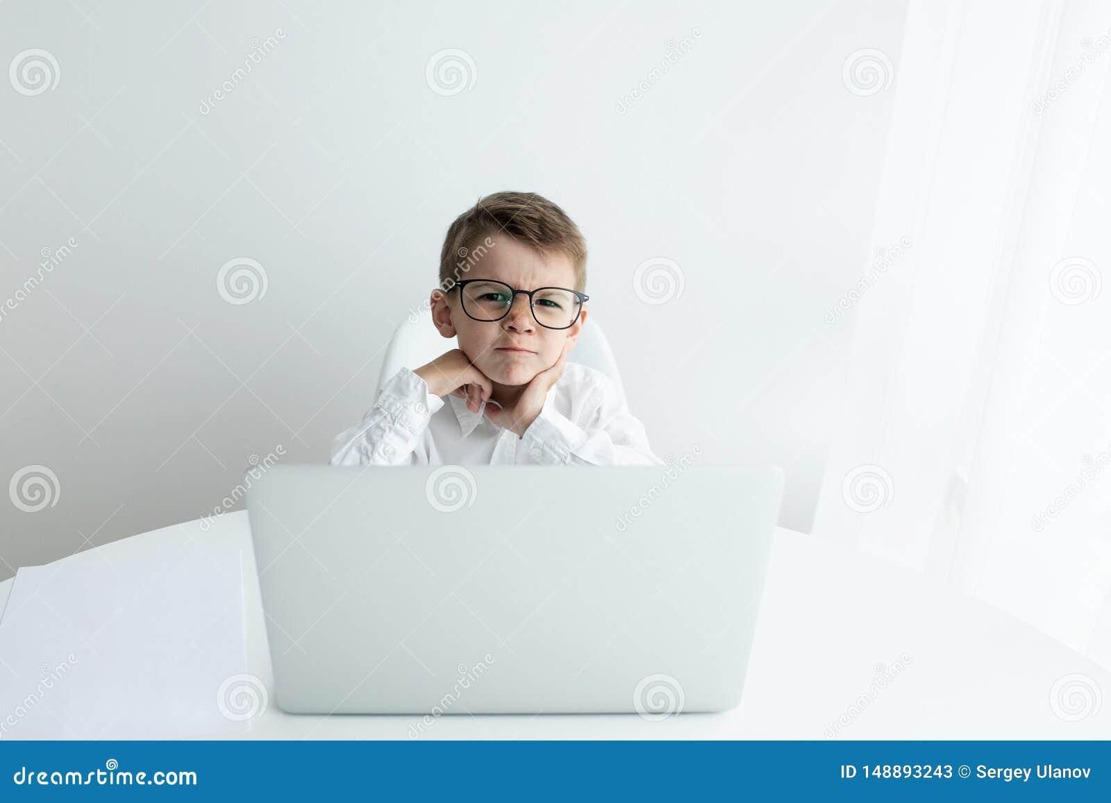 使用膝上型计算机的逗人喜爱的小男孩,当做家庭作业反对白色背景时