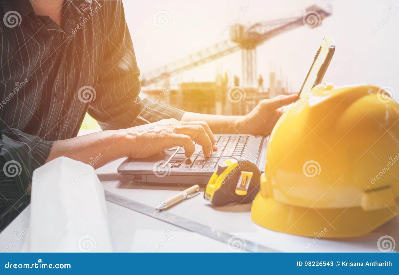 使用膝上型计算机的建筑师工程师为与黄色盔甲一起使用,